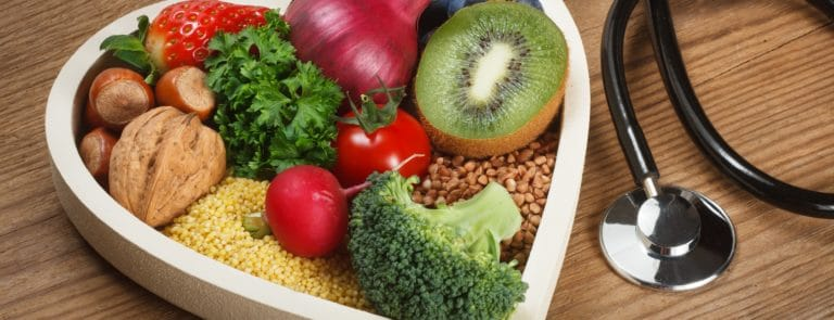 Healthy food in heart shaped bowl and stethoscope. Food such as blueberries, red onion, strawberry, parsley leaves, hazelnuts, walnut, tomato. kiwi, millet, buckwheat, radish, broccoli.