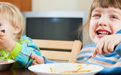 Two Children Eating And Smiling