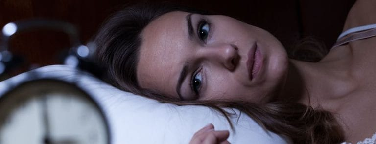 A person trying to sleep staring at an alarm clock