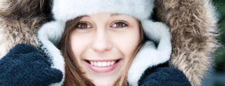 A women smiling in a hat and winter clothes