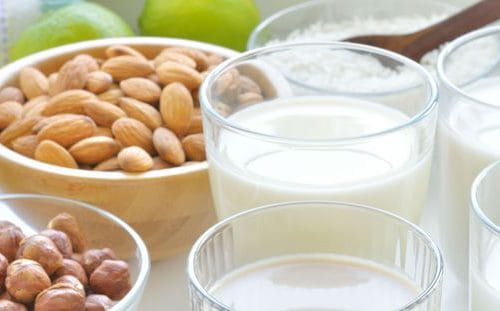 Glasses of Milk next to Almonds and other Nuts