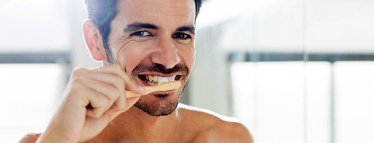 A man smiling whilst brushing his teeth