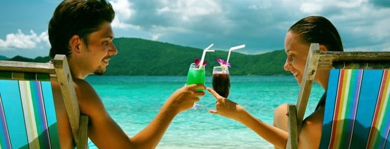 A couple drinking in on a beach while sunbathing