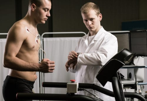 Doctor is supervising the athlete on a treadmill