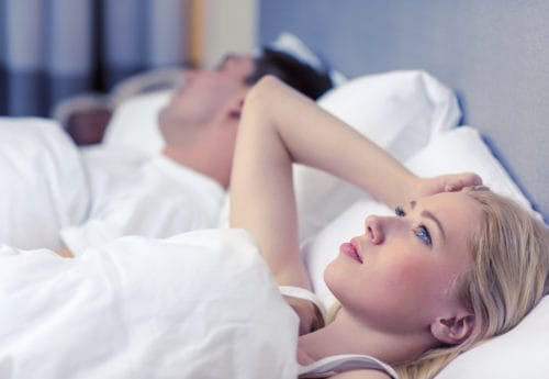 Woman lying in bed unable to sleep
