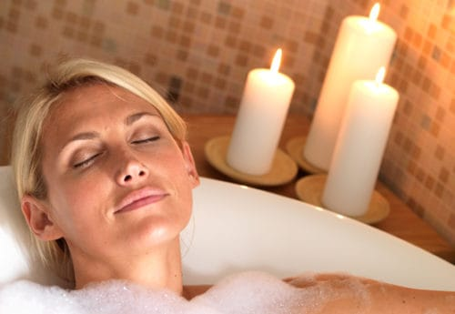 A women lay in a bath relaxing with candles in the background