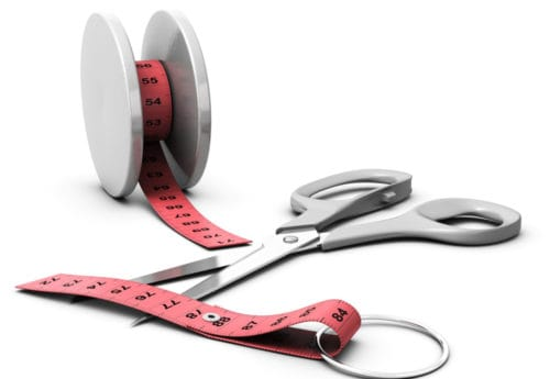 A tape measure that has been cut and a pair of scissors next to it