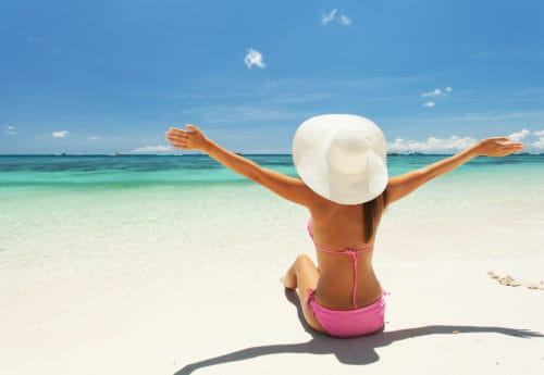 A women sat on a beach with a summer hat on and her arms stretched