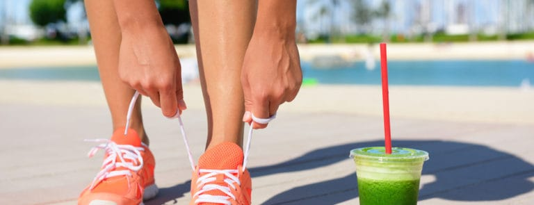 A women with a green smoothie tying her shoe laces