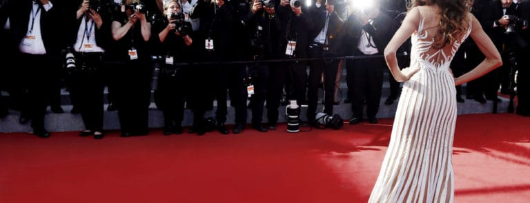 A Women being photographed by paparazzi at a red carpet event