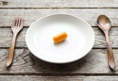 A plate with a baby carrot on it and cutlery