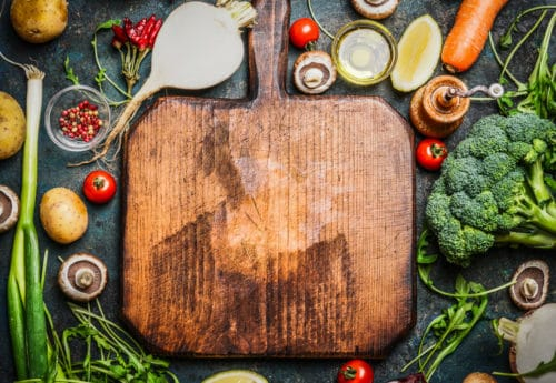 Wooden chopping board with different vegetables around the board