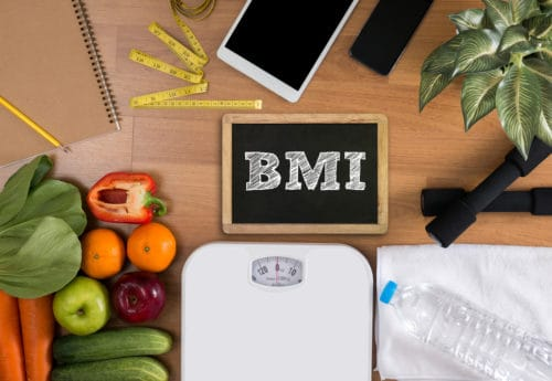 BMI written on a chalk board with fruit and veg, scales and office items near it