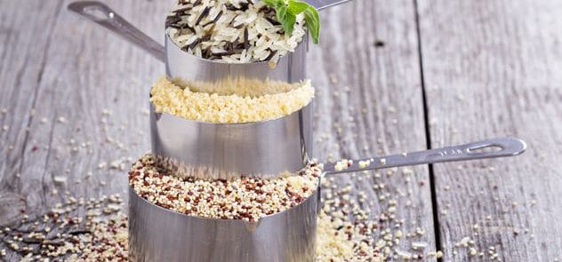 Three measuring cups with rice, grains and seeds in them