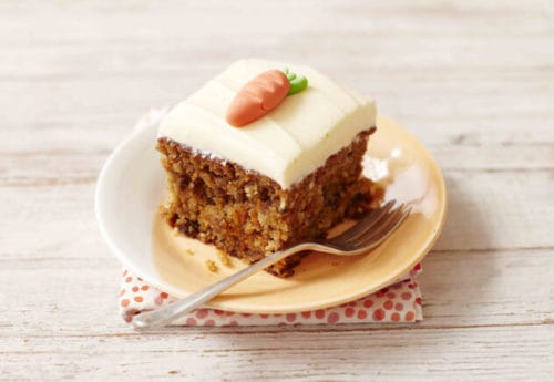 A slice of dairy free carrot cake with icing decoration