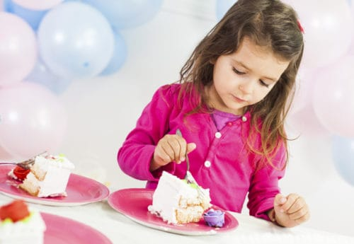 A child eating a slice of cake surrounded by ballons