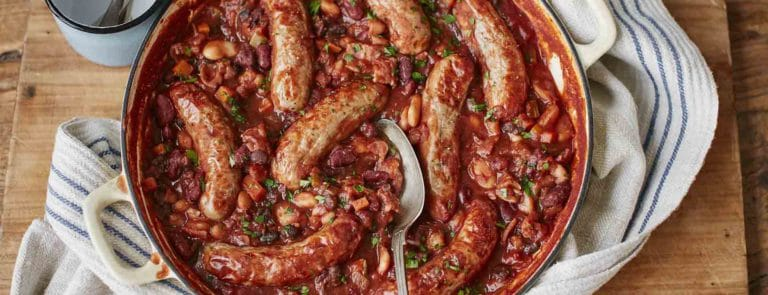 A dish with a bean and sausage casserole in it