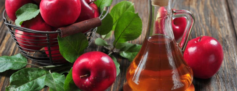 A jug of apple cider vinegar next to a basket of apples
