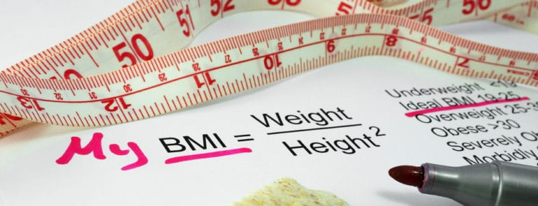 Paper with My BMI = Weight over Height squared written on it, with a tape measure