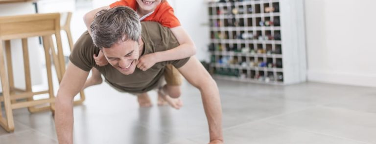 A dad doing Press ups with his son on his back