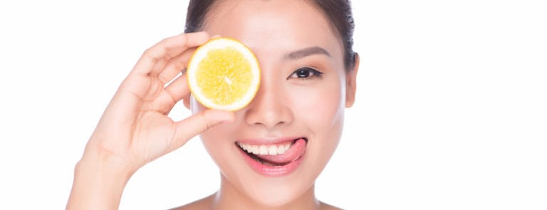 A women smiling with a lemon in front of her eye