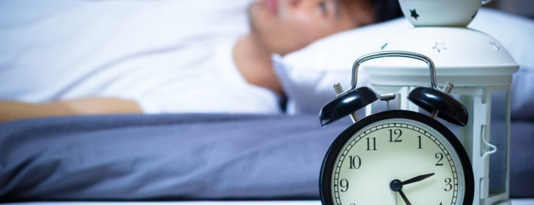 A man lay in bed not being able to sleep with a clock on the side