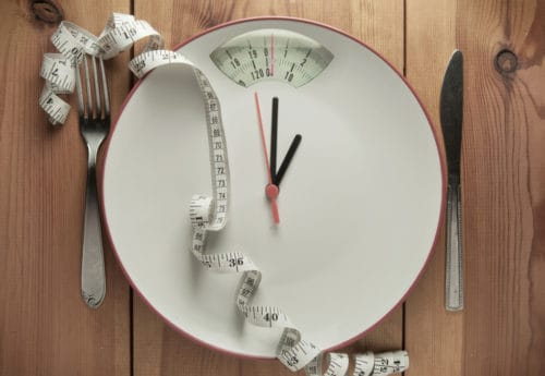 A scale with a clock on and a tape measure