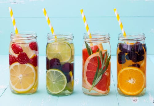 Jars cotaining different fruits and water with straws sticking out