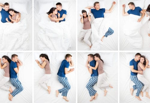 A couple lay in bed showing different sleeping positions