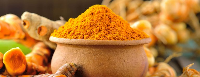 A pot of Turmeric spice or powder and Turmeric roots