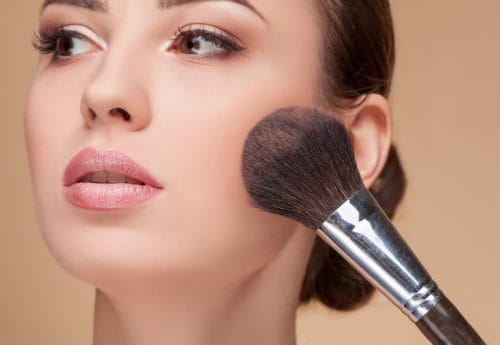 A women applying make up with a make up brush