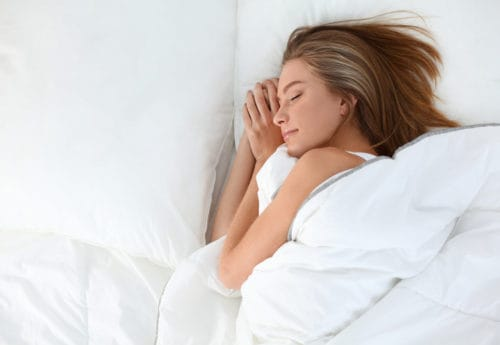 A women lay on her side sleeping in bed