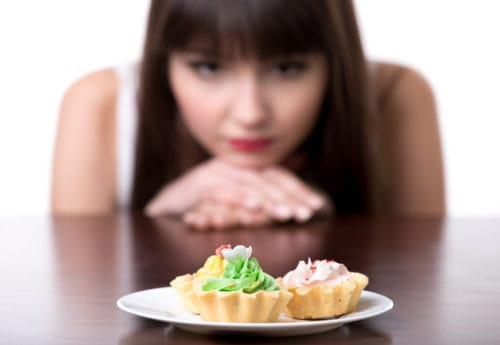 A women looking at a number of cakes and tarts