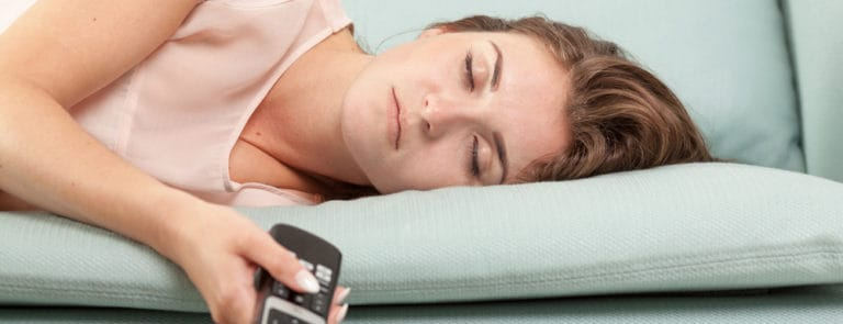 Young woman lying on couch and sleeping with TV remote control,