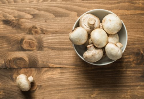 Bowl of raw mushrooms on wooden table