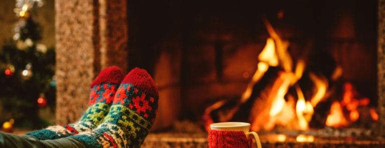 Feet in woollen socks by the Christmas fireplace