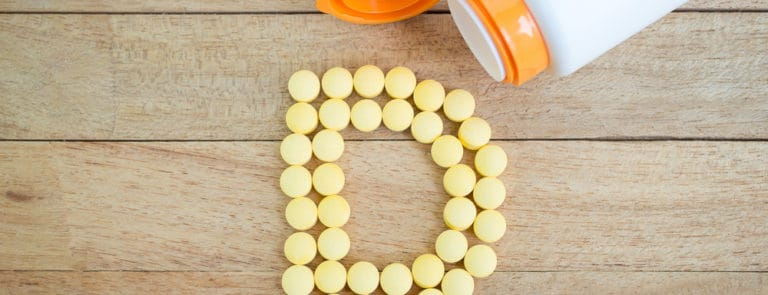 Vitamin D pills forming a D shape on a wooden background