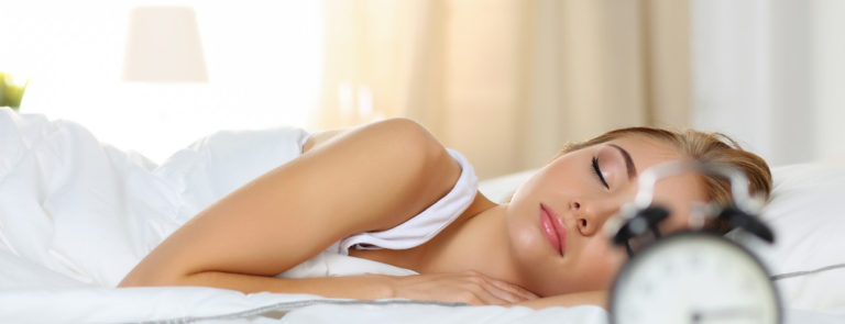 woman peacefully lying in bed sleeping early morning while alarm clock going to ring awakening.