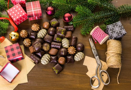 Wrapping assorted chocolates in small boxes for Christmas presents
