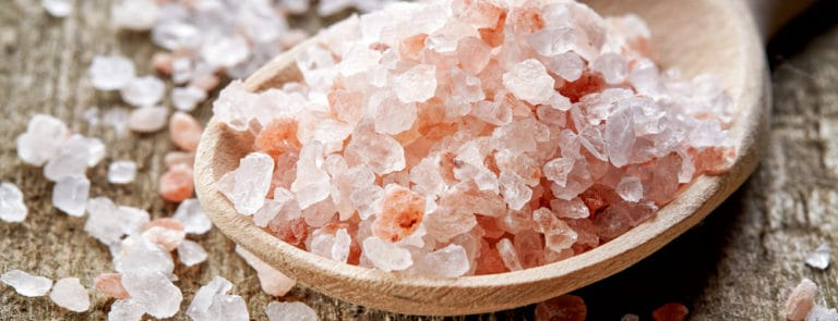 spoon of pink himalayan salt on wooden table
