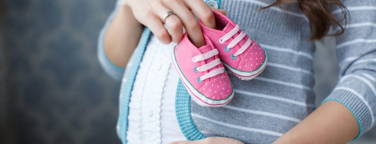 Small shoes for the unborn baby in the belly of pregnant woman.