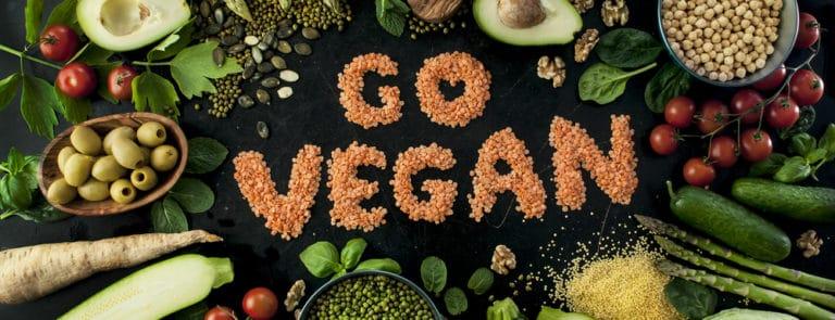variety of fresh green organic vegetables & lentils on dark background.