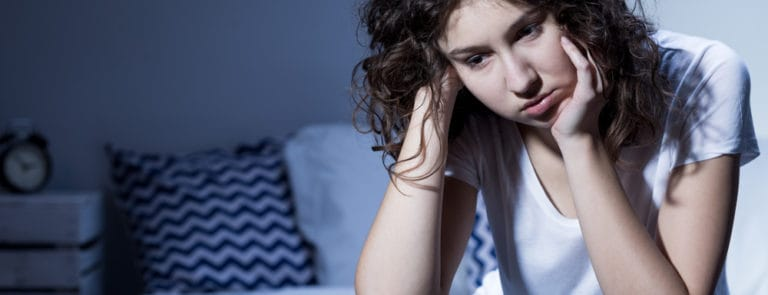 Close-up of a young woman in pyjamas sitting sleepless on the edge of her bed in the middle of the night