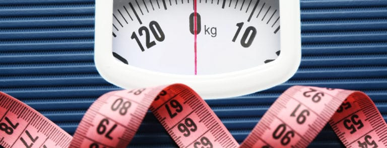 Bathroom scale with measuring tape on white background.