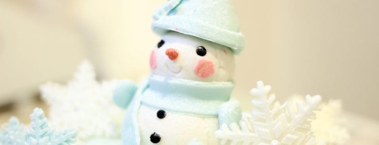 Snowman decorated with a Hat and blue scarf