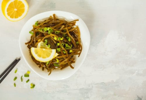 Sea kale kelp salad with oil in a white plate, top view, white background. Healthy vegan food concept.