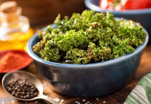 crispy kale in a bowl sat on a wooden table with oil, spices and peppercorn around it