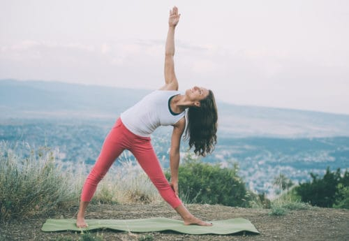 Young woman practicing yoga outdoor in the nature with city on background.