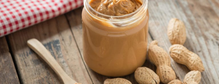 Creamy peanut butter on wood table.