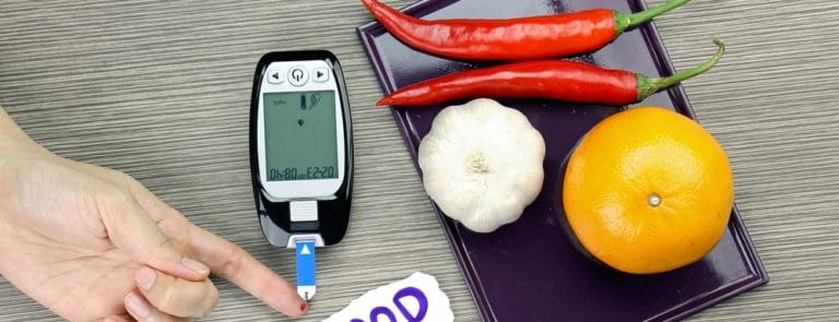 Blood sugar measurement, Diabetic kit, Blood glucose meter test and herbs. Healthy food eating concept. Orange, Garlic, Chilli.
